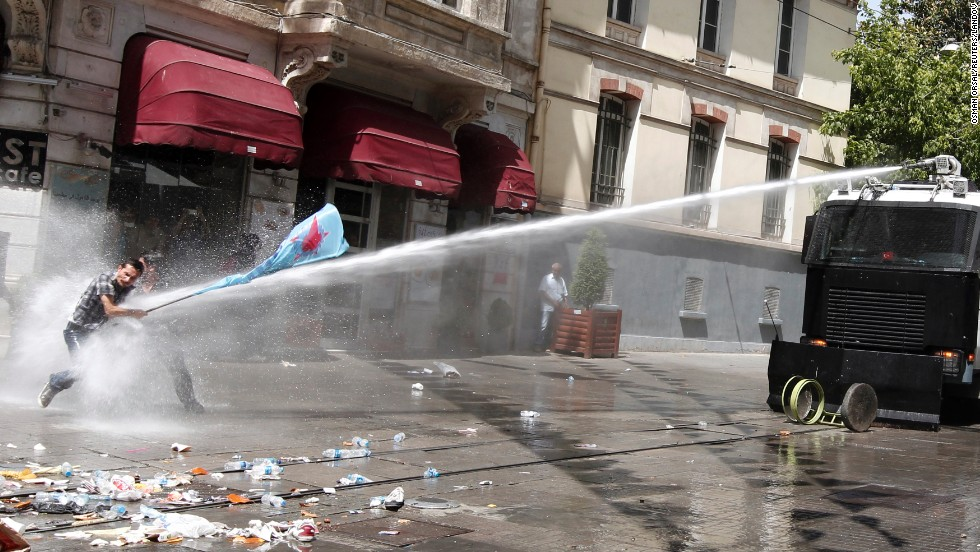 Protestors brace themselves as they are fired upon with a water canon by Turkish police forces.