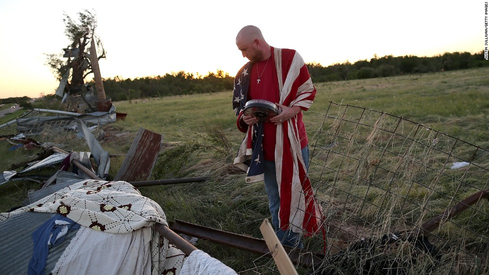 Mark Reynolds sifts through debris to salvage personal items in El Reno on Saturday, June 1.