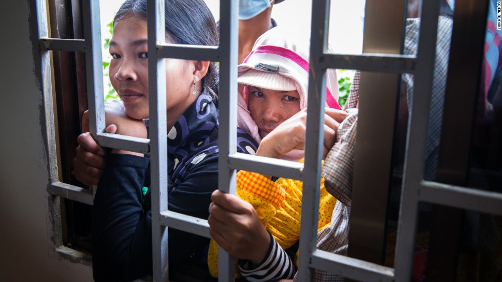 Workers look through a window, while their representatives negotiate their terms