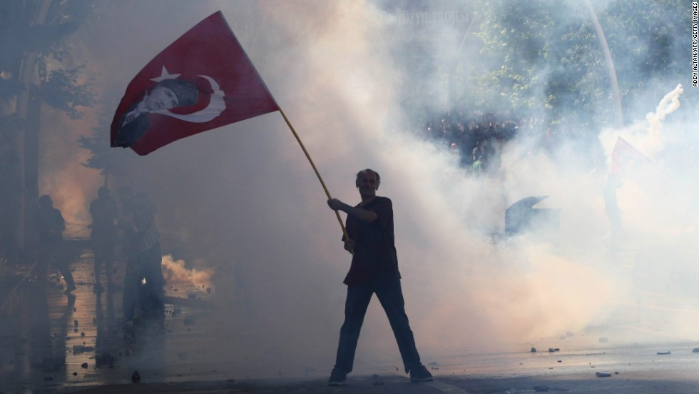 "JUNE 3 - ISTANBUL, TURKEY: Tear gas surrounds a flag waving protestor on June 1, 2013. What began as a small sit-in over the Turkish government's plan to demolish a park in central Istanbul in favor of a shopping arcade has swelled to become the biggest <a href=""http://cnn.com/2013/06/03/world/europe/turkey-protests/index.html?hpt=hp_t1"">protest movement against PM Recep Tayyip Erdogan</a> during his decade in power."