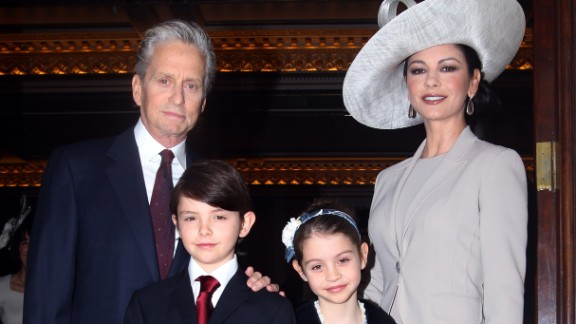 """British-born actress Zeta-Jones, right, arrives with Douglas and their children Dylan, left, and Carys in 2011 at Buckingham Palace in London. In January, Douglas announced in a """"Today Show"""" interview that his cancerous tumor is gone."""