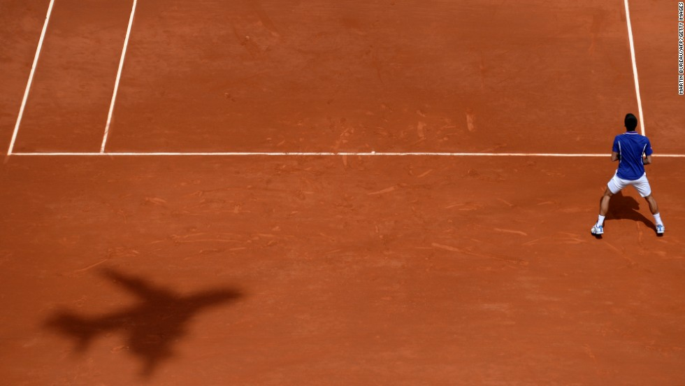 The shadow of a plane-shaped camera appears on the court as Djokovic waits for a serve from Kohlschreiber on June 3.