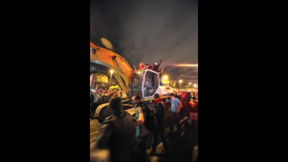 Protesters drive an excavator toward Turkish riot police as they make their way to Erdogan