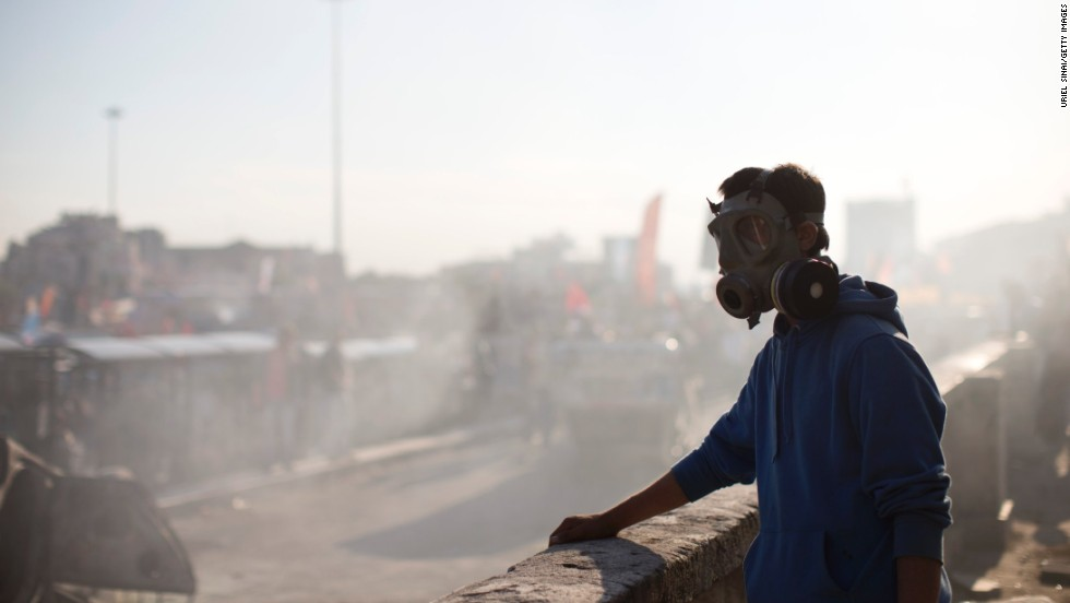 A protester wears a gas mask as smoke from a burned car fills the air at Taksim Square on June 3.