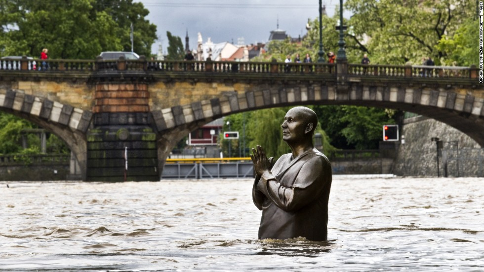 A statue by British sculptor Kaivalya Torpy depicting Indian spiritual leader Sri Chinmoy is partially submerged by the rising waters of the Vltava River on June 2 in downtown Prague.