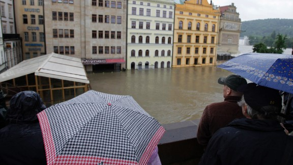 Onlookers watch the water rise around houses on the Vltava River in Prague. The Vltava was cresting Tuesday in the Czech capital, but areas downstream still faced rising waters.