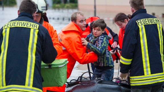 Firefighters and helpers evacuate citizens in the flooded city center in Grimma, Germany.