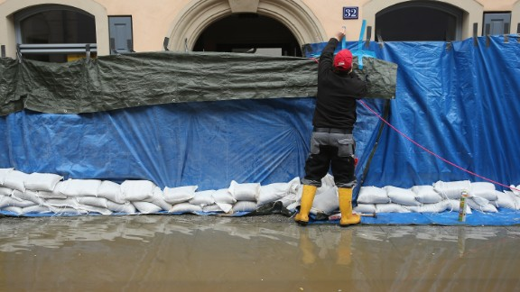 A resident adds a tarp to a restaurant on June 4, to help prevent damage from rising floodwaters from the nearby Elbe River in Pirna, Germany.
