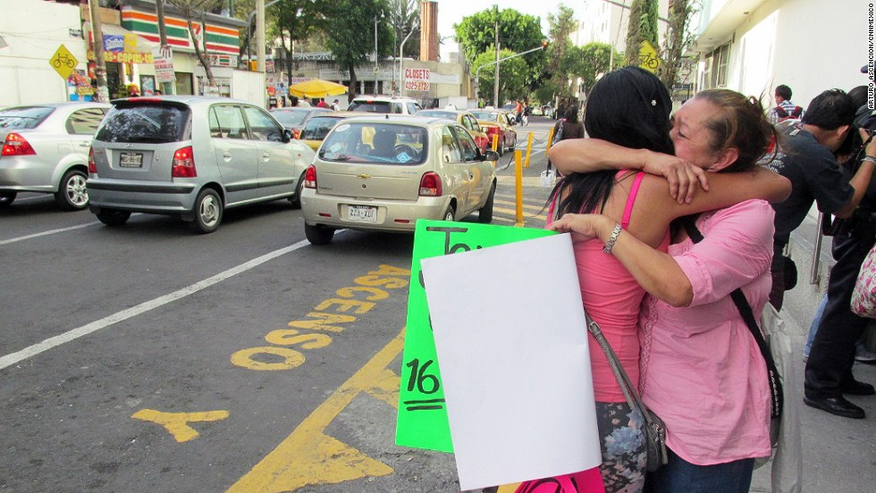 Family members of Jerzy Ortiz Ponce embrace one another while holding signs for the missing on May 31 in Mexico City.