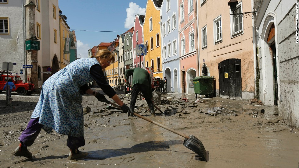 A woman cleans mud from the footpath in front of her house following flooding along the Inn River in Schaerding, Austria, on Wednesday, June 5. Rising rivers menaced swaths of Germany, the Czech Republic and Austria on Tuesday, as floodwaters inundated historic cities and forced mass evacuations of low-lying areas.