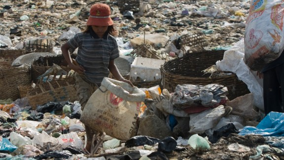 Sreyna picks through garbage -- the most desirable items are silver-colored metal and clear plastic.