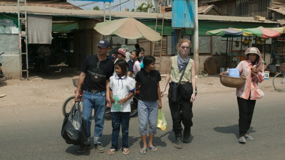 """Lauren Smith with Sreyna and Salim after a shopping trip in Cambodia. She says it didn't take much to buy clothes for the girls. """"You can get something for $2,"""" she says."""