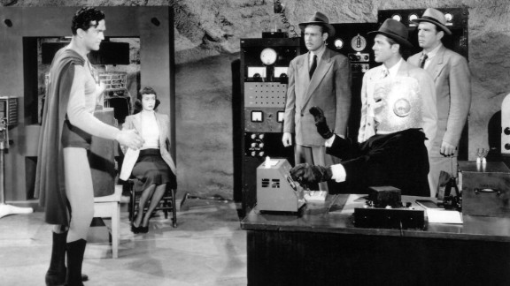 """Alyn revisits his role as Superman in the 1950 film serial """"Atom Man vs. Superman."""" Lyle Talbot, seated at right, plays the supervillain Lex Luthor, the Atom Man."""