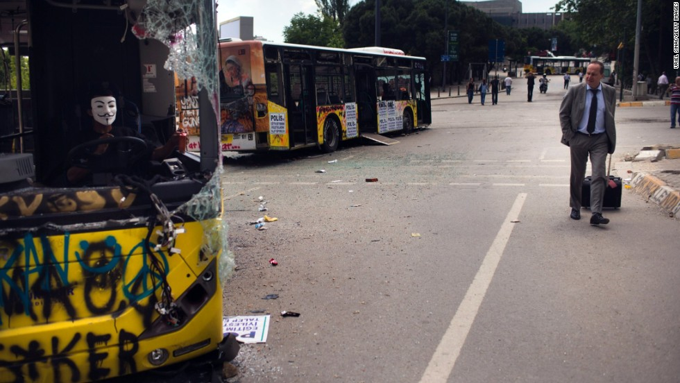 A man walks past damaged buses near Taksim Square on Thursday, June 6, in Istanbul, Turkey.