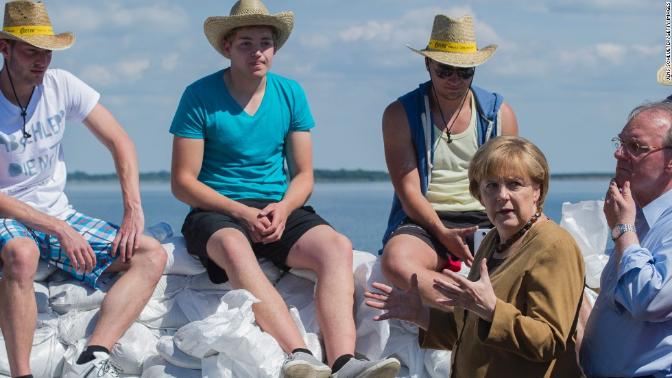 German Chancellor Angela Merkel and Reiner Haseloff, right, premier of the German state of Saxony-Anhalt, speak with volunteers about building a sandbag barrier near Lake Goitzsche in Bitterfeld-Wolfen, Germany, on June 6.