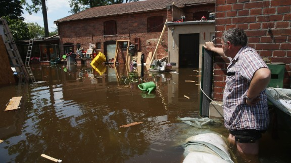 A resident wades to a neighbor's house on a flooded street near the swollen Elbe River on Friday, June 7, in Elster, Germany.