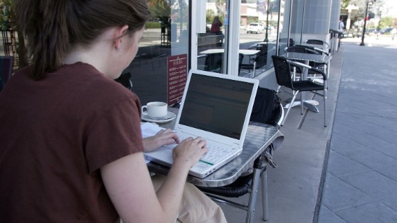 A woman uses free Google WiFi while sitting outside of a cafe August 16, 2006 in Mountain View, California.