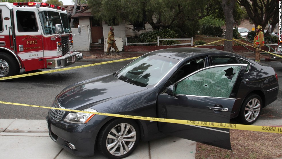 A car with windows shattered by bullets sits in front of a partially burned house where two bodies where found.  Authorities believe the incident may be related to the shooting on the campus of Santa Monica College.