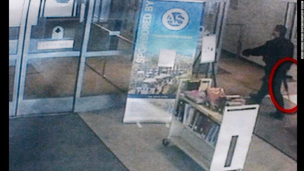 The gunman, carrying what appears to be an assault rifle (circled), enters the library.