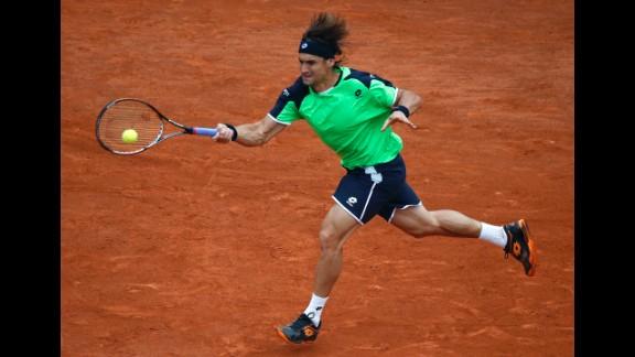 Ferrer returns a shot to Nadal.