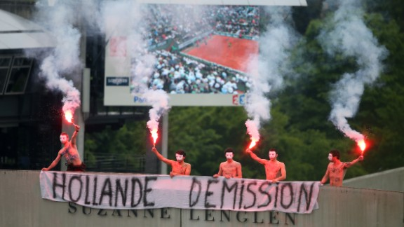 Protesters light flares and unfurl a banner which calls for the French President Francois Hollande's resignation on the top of Court Suzanne Lenglen as Nadal and Ferrer compete.