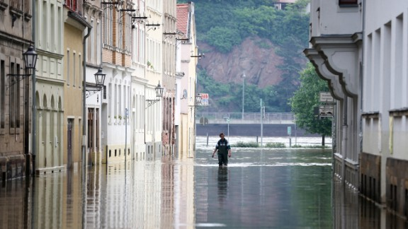 A man walks in high water from the Elbe River in Meissen, Germany, on Sunday, June 9.