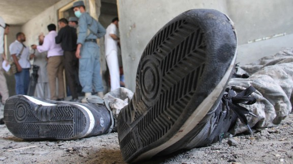 Afghan security officials inspect the body of a Taliban militant on June 10.