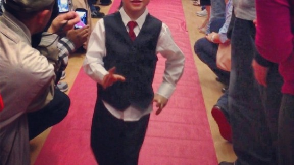 """Turns out lots of preschools have proms! Calvin Coursen struts the red carpet at his preschool prom at Kiddie Academy of Eatontown in Eatontown, New Jersey. """"I personally loved seeing my son dressed up and so excited to be with all his friends,"""" said mom Gwendolyn Coursen."""