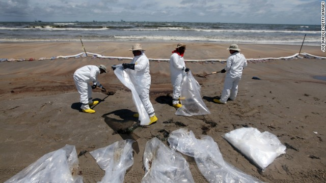 Workers in June 2010 clean up on Fourchon Beach in Louisiana after the Deepwater Horizon spill.