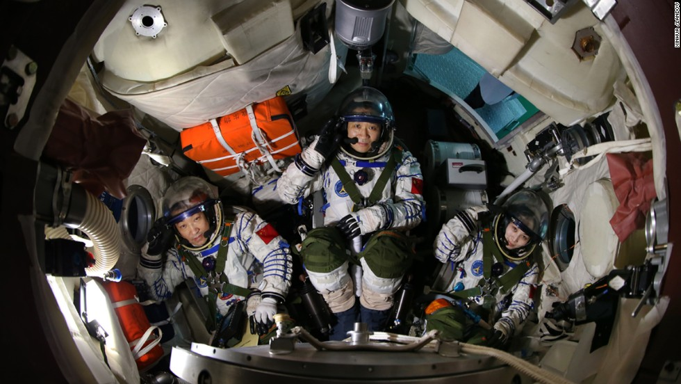Xiaoguang, left, Haisheng and Yaping sit in a simulated spaceship capsule on April 29.