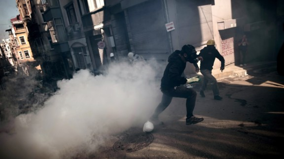 Protesters run from smoke as they clash with police in Istanbul on June 11.
