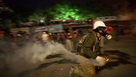 A protester prepares to throw a tear gas canister back toward police in Taksim Square on Tuesday, June 11.