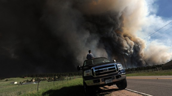 Andrew Dunlap and his father, Dave Dunlap, watch as a wildfire burns behind their house in Colorado Springs on June 11.