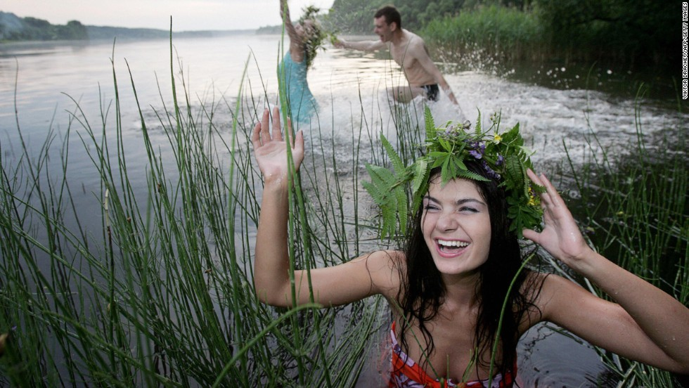BELARUS: People bathe in the lake of Vyacha during 'Ivan Kupala Day', a traditional Slavonic holiday celebration in Mochany village, 25 km outside Minsk, early 07 July 2006. During the celebration originating from pagan times, people plait wreaths, jump over fires and bathe.