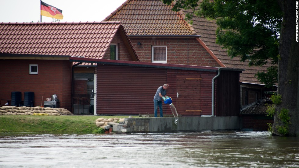 A man empties a bucket of water in front of his house in Hohnstorf, Germany, on June 12.