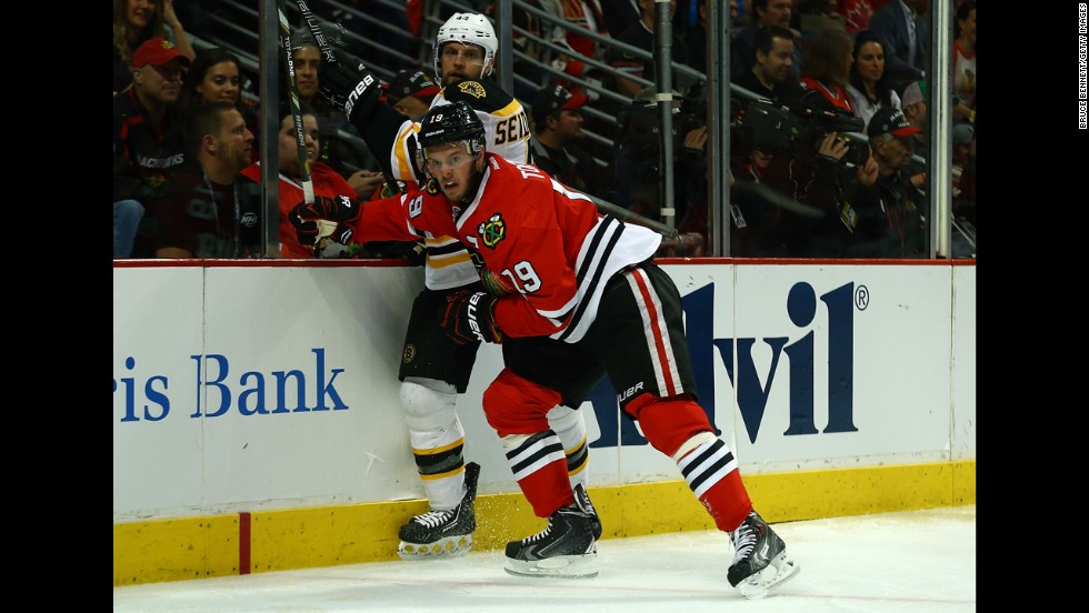 Jonathan Toews of the Chicago Blackhawks pushes past Dennis Seidenberg of the Boston Bruins.