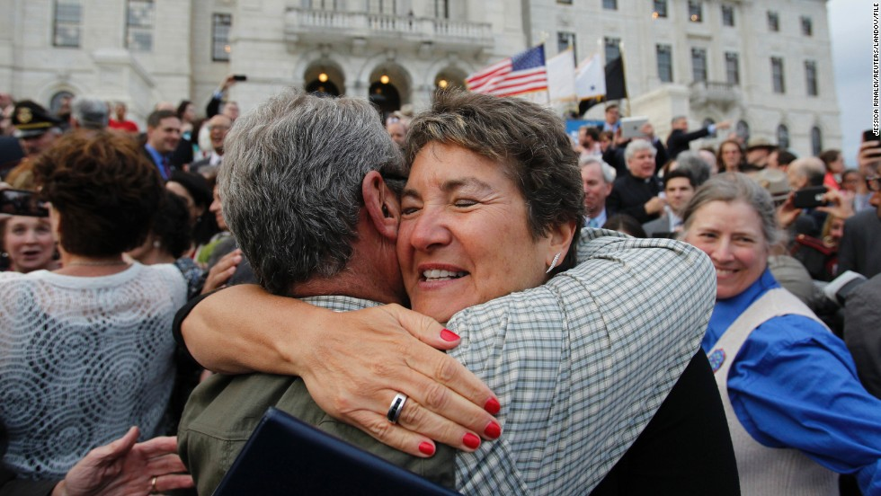 Rhode Island state Sen. Donna Nesselbush, right, embraces a supporter after the Marriage Equality Act was signed into law at the statehouse in Providence on May 2, 2013.