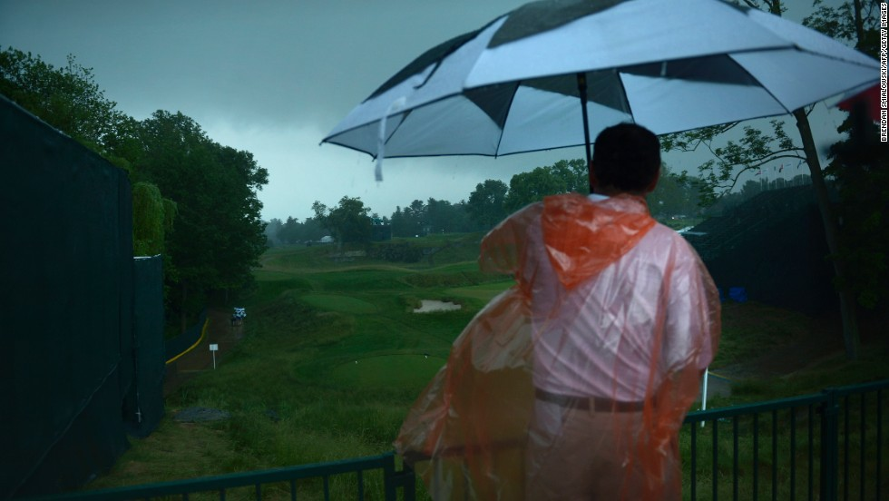 A man looks out over the 18th hole after play was suspended during a storm on June 13.