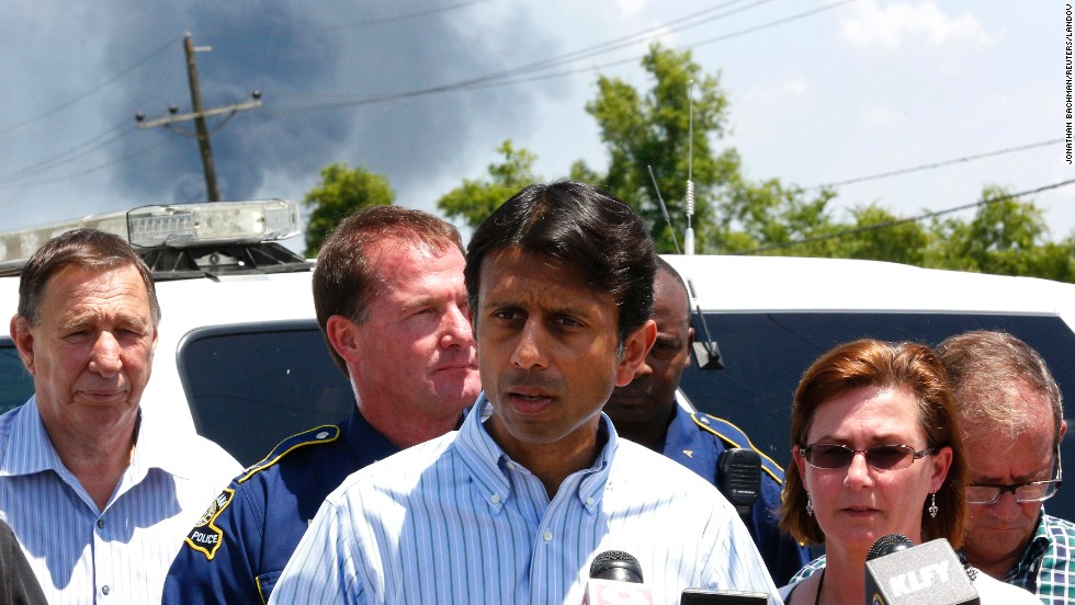 Smoke rises behind Louisiana Gov. Bobby Jindal as he talks about the explosion.
