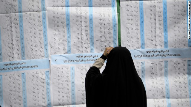 A woman looks over the ballot before casting her vote in Iran's presidential elections at a polling station in Tehran, on Friday, June 14.