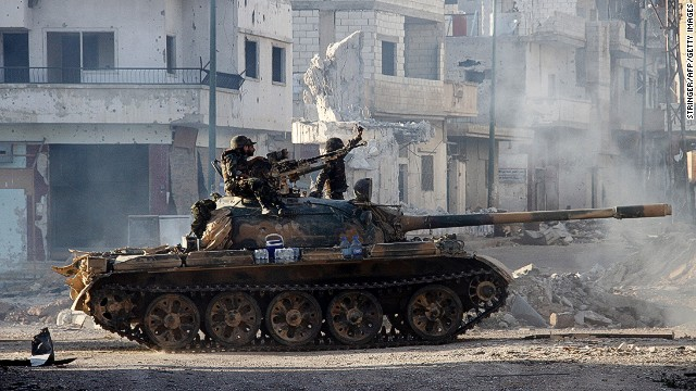 Syrian army troops drive through the ravaged streets of Qusayr in the central Homs province on June 5, 2013.