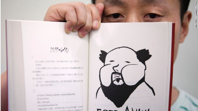 "Author Du Bin poses with his book ""God Ai,"" said to be the first biography of dissident artist Ai Weiwei."