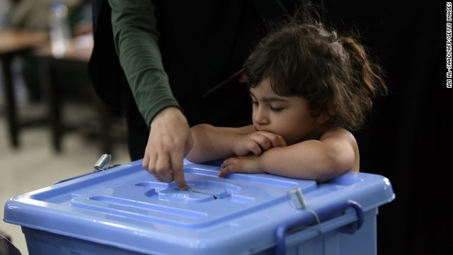 A young girl looks at an Iranian national casting her ballot as she votes on June 14.