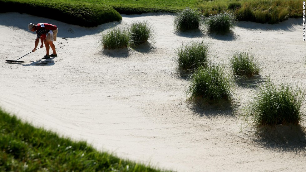 A caddie rakes a bunker at the 10th hole on June 15.