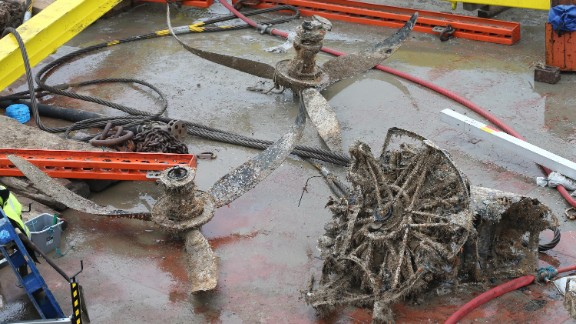 Seawater-damaged engine parts and propellers of the aircraft sit on a salvage barge.