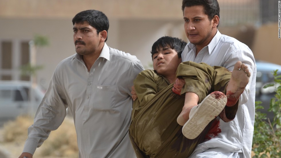 A man carries an injured boy after the hospital attack. Seven people have killed in the siege of the hospital.