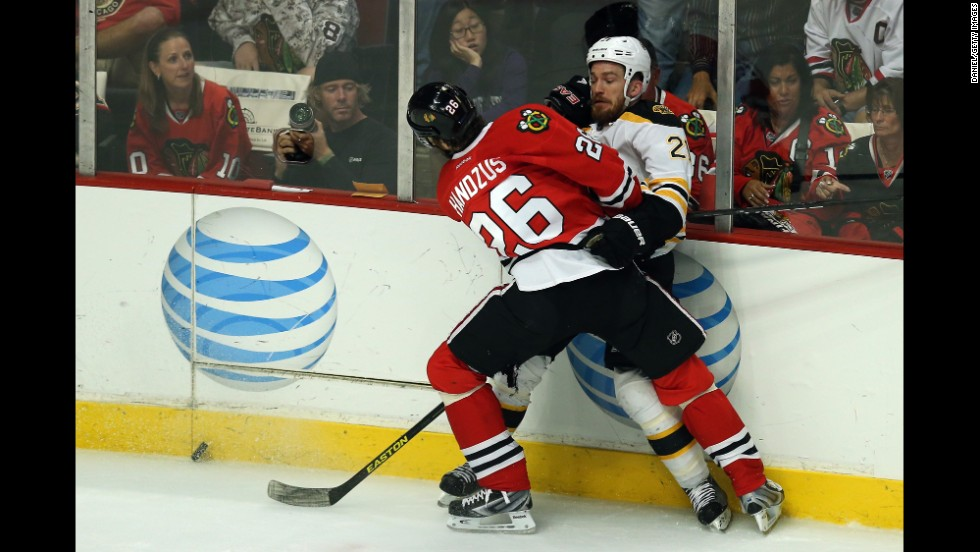 The Blackhawks' Michal Handzus  checks Andrew Ference of the Boston Bruins.