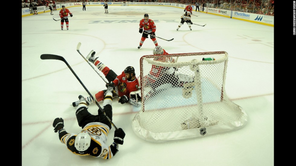 Brad Marchand of the Boston Bruins falls to the ice as Corey Crawford of the Chicago Blackhawks tends goal.