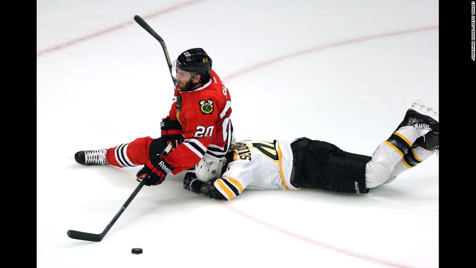 Brandon Saad of the Chicago Blackhawks falls to the ice on top of Dennis Seidenberg  of the Boston Bruins.