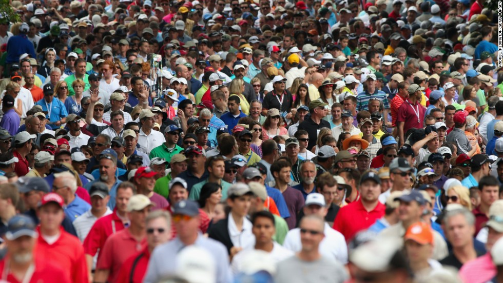 A gallery of fans follows Tiger Woods and Matt Bettencourt of the United States near the second hole during the final round on June 16.
